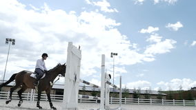 The guy jumping over the barrier at the horseback stock video