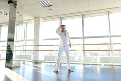 Dancer jumping  with close up air kiss. Guy jumping  and sending close up air kiss. Male person wears white suit. Concept of dance school and promotion Royalty Free Stock Images