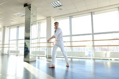 Dancer jumping  with close up air kiss. Guy jumping  and sending close up air kiss. Male person wears white suit. Concept of dance school and promotion Royalty Free Stock Image