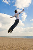 Guy jumping into the sky. Young guy jumping high on the beach like he is flying into the sky Royalty Free Stock Photo