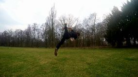 Guy jumps backflip in the park, slowmotion stock footage