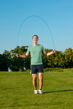 Guy jumps on a skipping rope on a green meadow. Stock Images