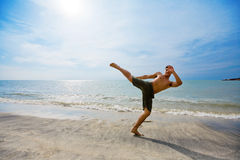 Guy kick boxing by the beach. A energetic guy kick boxing by the beach in beautiful sky Stock Photos