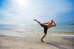 Guy Kick Boxing By The Beach Stock Photos