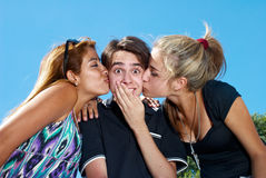 Guy kissed by two attractive girls. Outdoor Stock Photos