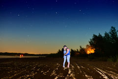 The guy kisses the girl on the beach at night Royalty Free Stock Photos