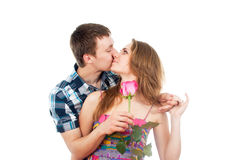 Guy kisses a girl with a rose Royalty Free Stock Images