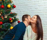 Guy kisses a girl under the tree on Christmas Royalty Free Stock Photography