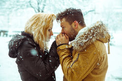 Guy kisses the hand of a lady in the snow Stock Photo