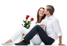 Guy kissing his girfriend who holds red roses Royalty Free Stock Images