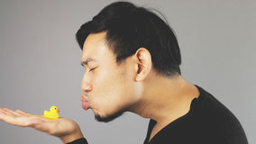 A guy kissing a rubber duck. An asian man with black t-shirt stock photography