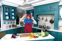 Guy at kitchen dressing apron and hat. Chef wears red uniform. Man dressed on red hat on hand. stock photography