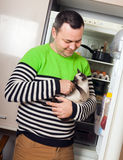 Guy with kitten near  refrigerator Stock Images