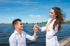 The guy is kneeling before the girl on a wooden pier near the wa Stock Images
