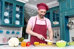 Guy with knife cutting orange pepper on table. Cook dressed in apron prepare dinner with paprika. Man in hat preparing vegetables. Man in hat preparing royalty free stock images