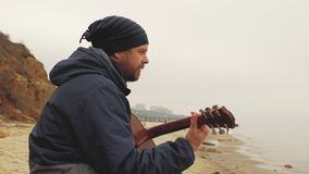The guy in the knitted hat sits on a stone and plays the guitar.playing guitar view from abovea guy with a beard playing a guitar stock video footage