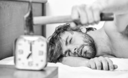 Guy knocking with hammer alarm clock ringing. Break discipline regime. Annoying sound. Stop ringing. Annoying ringing. Alarm clock. Man bearded annoyed sleepy stock photos