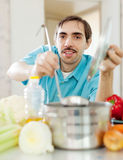 Guy with ladle cooking vegetables soup at kitchen Stock Photography