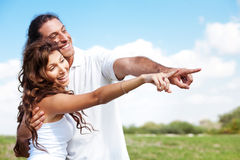 Guy and lady pointing while standing in the nature Royalty Free Stock Photo