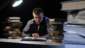 Guy in the lamplight, and reading a book. Black background stock video footage