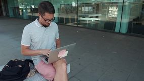 Guy with laptop outdoor. Casual urban man sitting on a bench by the building in shadow with a laptop with sticker on a lid. Guy sitting online from laptop stock footage