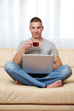 Guy with laptop and tea Stock Images