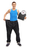 Guy in large jeans holding a weight scale. Full length portrait of a guy in large pair of jeans holding a weight scale isolated on white background royalty free stock photo