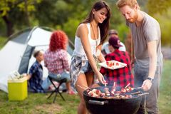 Guy and lassie putting grilled skewers on plate. Guy and lassie putting grilled colorful skewers on plate in forest royalty free stock image