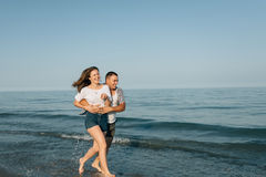 The guy in good mood embraces the girl. The guy, laughing, embraces to a devushuk against the background of sea waves Stock Images