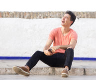 Guy laughing and sitting outside on sidewalk with cell phone Royalty Free Stock Images