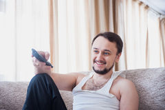 Guy laughs, sitting on the couch Royalty Free Stock Images
