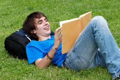 Guy laying on the grass and reading a book Royalty Free Stock Image