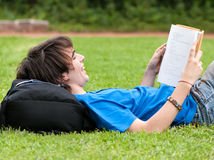 Guy laying on the grass and reading a book Royalty Free Stock Images