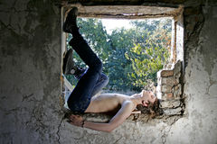 Guy is laying on the window opening Royalty Free Stock Photo