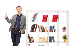 Guy leaning on a bookshelf and giving a thumb up. Young guy in a gray coat leaning on a bookshelf and giving a thumb up isolated on white background royalty free stock image
