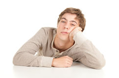 Guy leaning on table. Young man in grey blouse leaning on table, white background Royalty Free Stock Images
