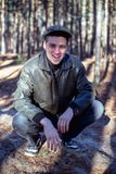A guy in a leather jacket and cap sits on a road in a forest royalty free stock photo