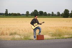 Guy in Leather Jacket Playing Acoustic Guitar on S Royalty Free Stock Photos