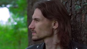 The guy in the leather jacket in the woods. Cool guy in a leather jacket in the woods among the pines stock video footage