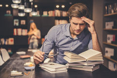 Guy in the library. Tired young men is holding eyeglasses and leaning over the pile of books while working hard in the modern library Stock Photos