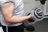 The guy lifts a dumbbell, is photographed by a close up Stock Images