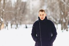 A guy with light short hair in a winter jacket poses to the came. Ra in winter Stock Image