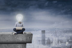 Guy with a lightbulb head on the roof Stock Photo