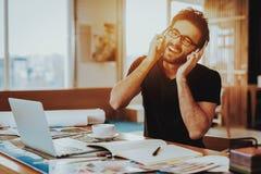 Guy Listen aan Muziek in Hoofdtelefoons op het Werk stock afbeeldingen