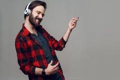 Guy Listening à música e à guitarra imaginária do jogo fotografia de stock royalty free