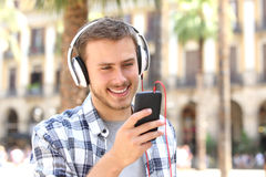 Guy listening music on line in the street. Front view of a happy guy with headphones listening music on line and watching media in a smartphone in the street Stock Image