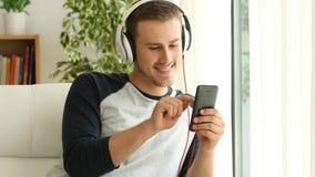 Handsome man choosing audio application on phone stock video video