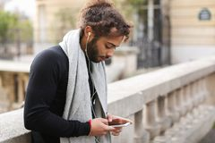 Mix blood music lover enjoying new earphones and smartphone  nea. Guy listening to music in white in ear headphones and new smartphone with Eiffel tower in Stock Image