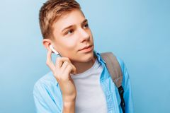 Guy is listening to music, wireless headphones, on a light blue background stock photos