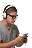 Guy Listening to Music. A young man listens to music with a set of head phones while examining the album cd case Stock Photos